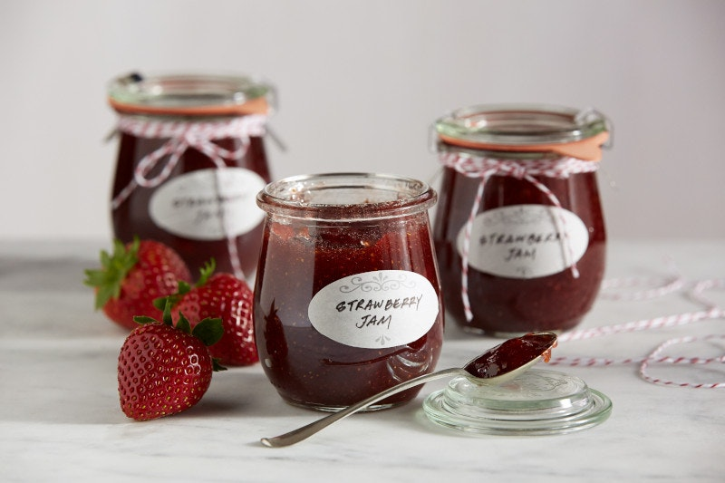 Three jars of small batch strawberry jams sitting next to three strawberries. A thin ribbon is tied around two of the jars.