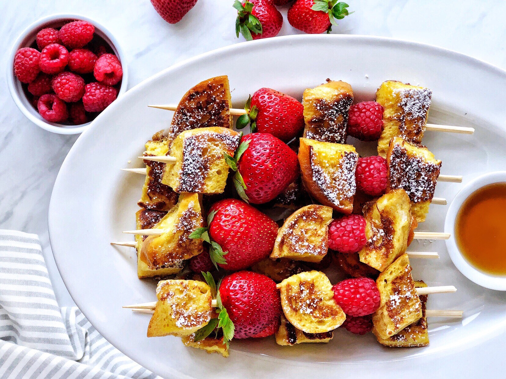 Berry french toast kebabs with french toast pieces, raspberries, and strawberries on a skewer