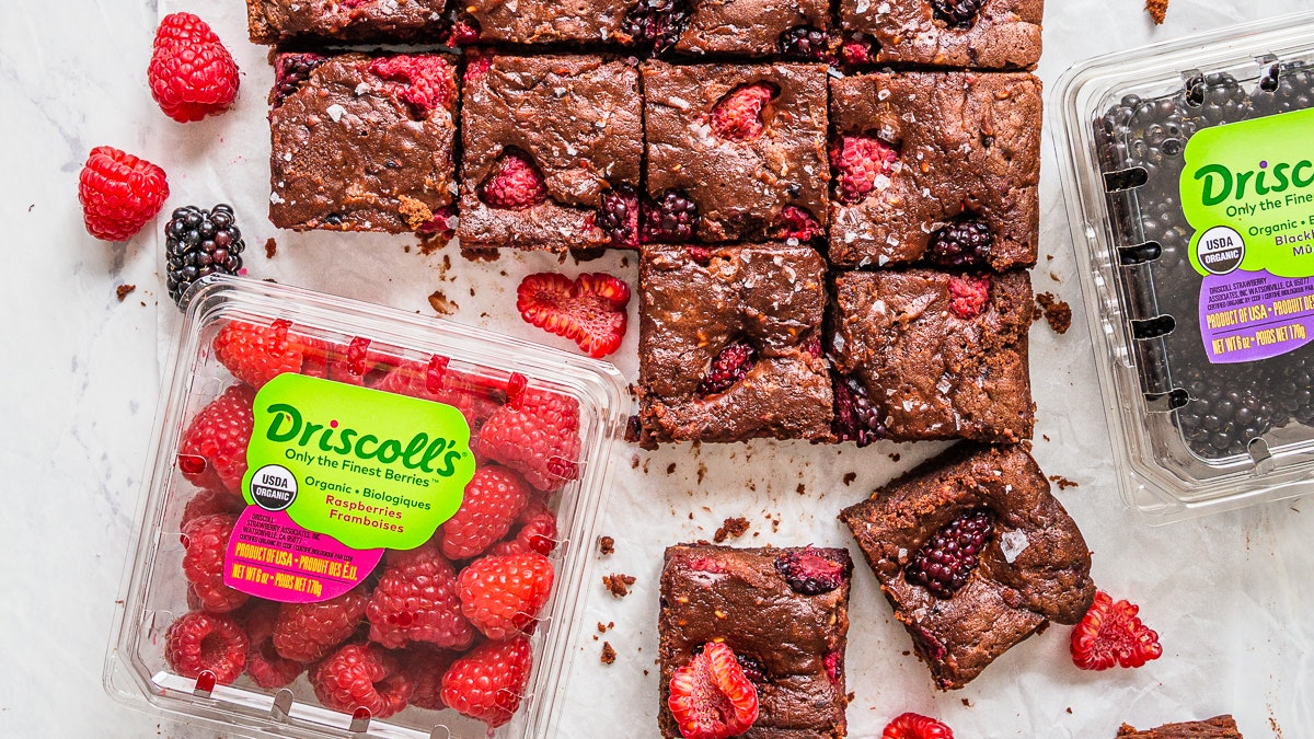 Squares of blackberry and raspberry brownies next to Driscoll's organic blackberry and raspberry clamshells.