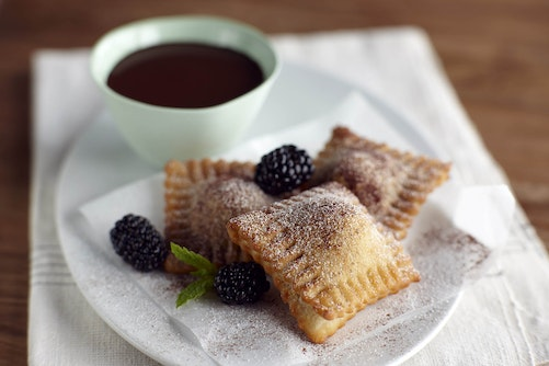 Plate of fried blackberry ravioli with chocolate fondue