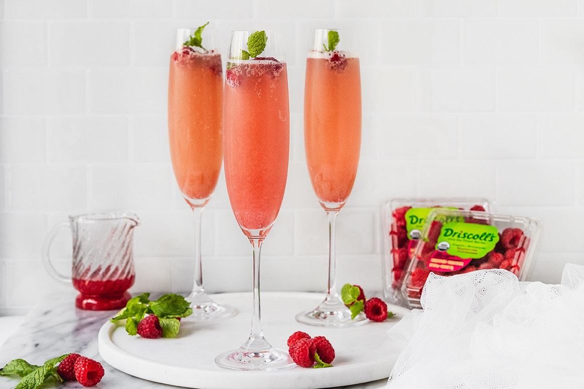 Raspberry mimosas topped with fresh raspberries and garnish. Driscoll's clamshells of organic raspberries along with a small container filled with raspberry sauce sit on the counter behind the champagne glasses. The raspberry mimosas are sitting on a white plate with raspberries and garnish scattered throughout the photo.