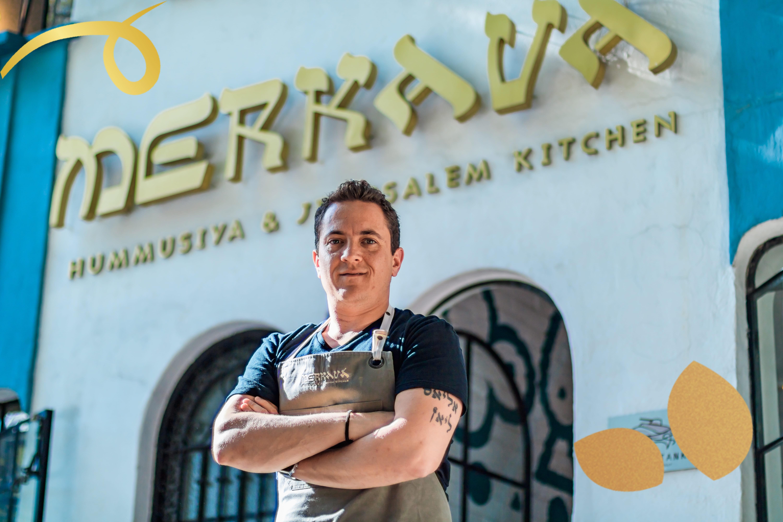 un chef enfrente de su restaurante